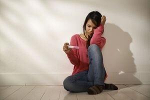 девушка с разочарованием смотрит на тест