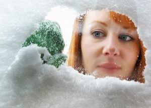 девушка смотрит через заснеженное окно
