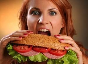 девушка ест большой бутерброд