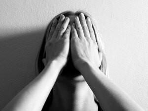 женщина закрыла лицо руками и находится в глубокой депрессии
