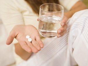 таблетки и стакан с водой в руках женщины