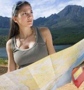 девушка держит карту, чтобы сориентироваться на местности