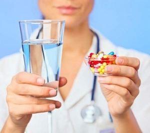 у врача в руках стакан с водой и таблетки