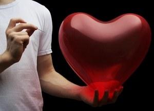 мужчина пытается проколоть иглой шарик в виде сердца