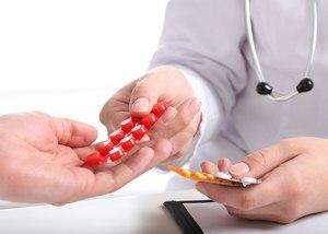 врач дает таблетки пациенту