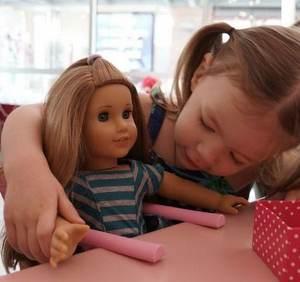девочка играет куклой