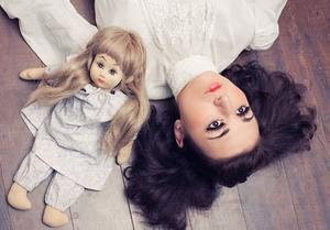 девушка лежит рядом с куклой
