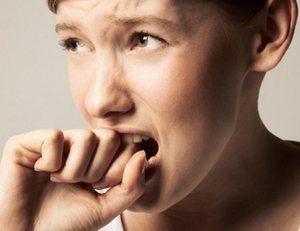 девушка кусает кулак из-за внутренних переживаний