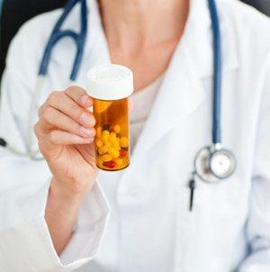 упаковка с капсулами в руках врача