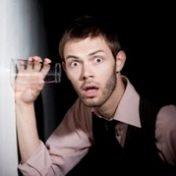 мужчина держит стакан у стены