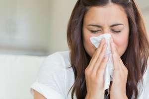 брюнетка вытирает нос салфеткой