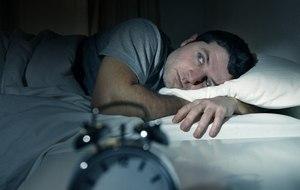 мужчина с открытыми глазами в постели