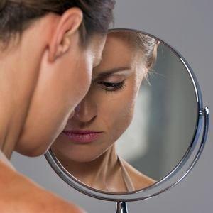 девушка недовольна изображением в зеркале