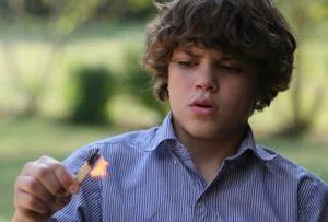 горящие спички у подростка в руках
